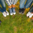 Legs and sneakers of teenage boys and girls standing in half circle on the grass - Stock Photo