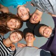 Six happy teenagers standing in the circle and looking down — Stock Photo