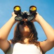 Teenage girl watching with binoculars on sunny summer day — Stock Photo