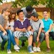 Teenage boys and girls having fun in the garden while sitting on the bench — Stock Photo