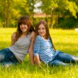 Two cute smiling teenage girls sitting on the grass on sunny spring day — Stock Photo