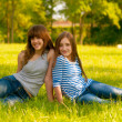 Two cute smiling teenage girls sitting on the grass on sunny spring day - Stock Photo