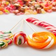 Four colorful lollipops and piles of candy in the background isolated on white. — Stock Photo