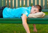 Sad lonely teenage boy lying on the bench — Stock Photo