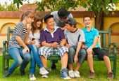 Teenage boys and girls having fun in the garden while sitting on the bench — Stockfoto
