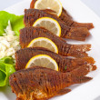 Постер, плакат: Fried fish with green salad onions and lemon slices