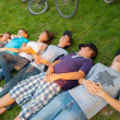 Teenage boys and girls lying on the grass after riding bicycles — 图库照片