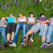 Teenage boys and girls lying in the grass after riding bicycles — ストック写真