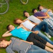 Teenage friends lying on the grass after riding bicycles — Stock Photo