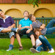 Bored teenagers sitting and lying on the bench on beautiful spring day — Stock Photo