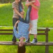 Stock Photo: Two teenage boys holding teenage girl upside down