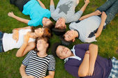Six teenage friends lying on the grass and having fun — Stock Photo