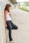 Lonely teenage girl leaning against concrete wall in urban environment — Stock Photo