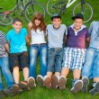 Happy teenage boys and girls resting in the grass after riding bicycles — Stock Photo