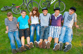 Happy teenage boys and girls resting in the grass after riding bicycles — Stockfoto