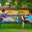 Two teenage boys sitting on the bench and throwing ball to each other — Stock Photo