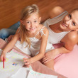 Happy mother and daughter drawing and having fun together — Stock Photo