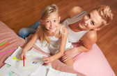 Happy mother and daughter drawing and having fun together — Stock fotografie