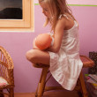 Sad lonely little girl sitting on small table in her room while holding baby toy — Stock Photo #13351003