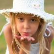Cute little girl on the meadow blowing a kiss toward you on beautiful summer day — Stock Photo
