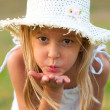 Cute little girl on the meadow blowing a kiss toward you on beautiful summer day — Stock Photo #13443902
