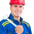 Portrait of young handsome mechanic with hard hat and in overalls holding wrench — Stock Photo