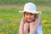 Cute elegant little girl sitting on the meadow on beautiful spring day — Stock Photo