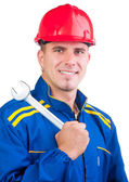 Portrait of young handsome mechanic with hard hat and in overalls holding wrench — Foto Stock