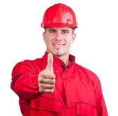 年轻的微笑着消防员与安全帽和在孤立的白色完全统一显示竖起大拇指. — 图库照片