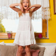 Cute little girl standing on the bed with surprised look on her face — Stock Photo