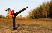 Beautiful kick boxing girl exercising high kick in the nature on sunny summer day. — Stockfoto
