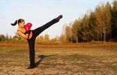 Mooie kick boksen meisje uitoefening van hoge schop in de natuur op zonnige zomerdag. — Stockfoto