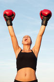 Victorious sports woman in red gloves against blue sky on sunny summer day. — Stock Photo