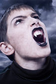 Portrait of fierce vampire with sharp long teeth on stormy night — Stock Photo