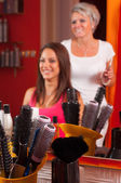 Hairdresser and beautiful girl having fun while making hair. Focus is on the combs and equipment in the bottom. — Stock Photo