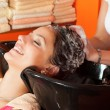 Beautiful young girl enjoying hair washing in hairdressing salon - Stockfoto