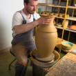 Craftsman making vase from fresh wet clay on pottery wheel - Stock Photo