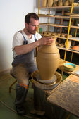 Craftsman making vase from fresh wet clay on pottery wheel — Stock Photo