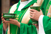 Christian priests holding bowls with wafer and wine during sacrament. — Stock Photo