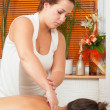Young massage therapist giving a massage in massage salon — Stock Photo #14141931