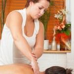 Young massage therapist giving a massage in massage salon — Stock Photo