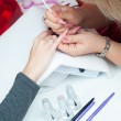Manicure process in beauty salon showing making of beautiful drawings on artificial nails — Stock Photo #14142090