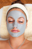 Beautiful young woman lying on massage table with natural facial mask on her face — Stock Photo