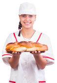 Glad kvinna baker i vitt enhetliga och gemensamma jordbrukspolitiken visar nybakade födde upp isolerade på vit. — Stockfoto