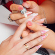 Manicure process in beauty salon showing filing and polishing of nails - Stock Photo