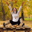 Beautiful happy girl sitting on the wooden table in the park and throwing leaves in the air — Stock Photo