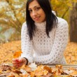 Cute smiling girl sitting in the park on beautiful autumn day and holding dry leaf — Stock Photo