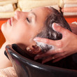 Stock Photo: Beautiful young girl enjoying hair washing in hairdressing salon