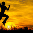 Silhouette of the running girl at sunrise - Stock Photo