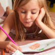 Cute blond little girl drawing on the paper while lying on bed. — Stock Photo #15524715